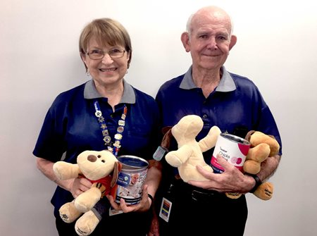 Mater volunteers Zofia and Errol hold Mater merchandise while smiling at the camera.