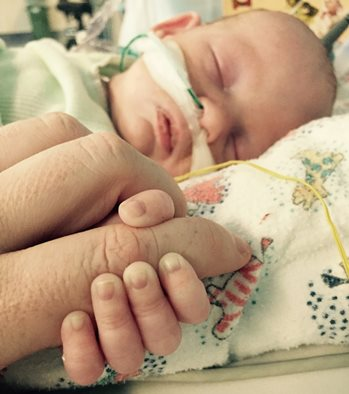 Baby Parker's face covered with feeding cable, holds hand with his mother.