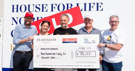 New home owners hold oversize cheque.